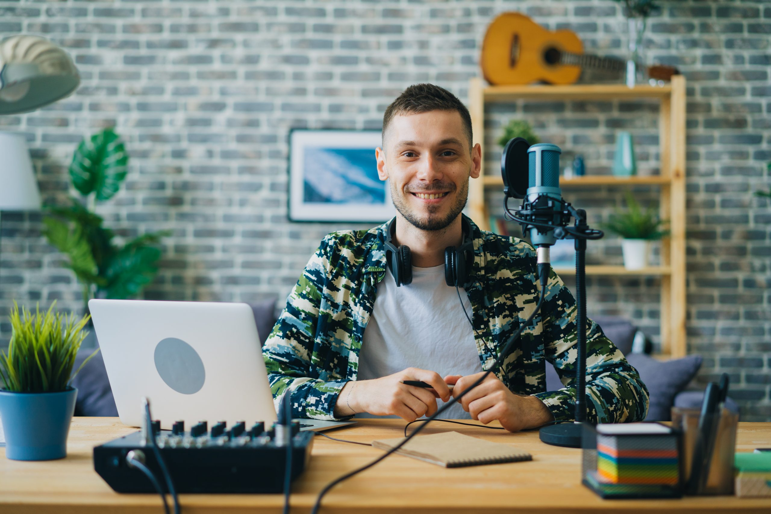 Portrait of young man blogger in recording studio sitting near microphone smiling looking at camera. Blogging, modern technology and people concept.